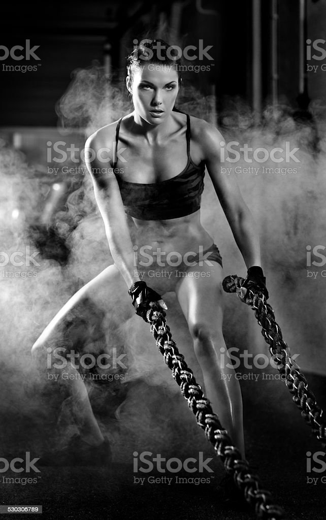 female athlete is battling ropes in gym stock photo
