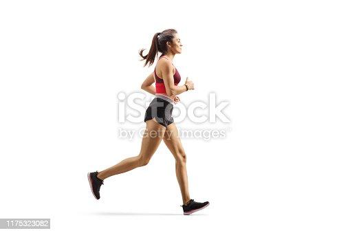 Full length profile shot of a female athlete jogging isolated on white background