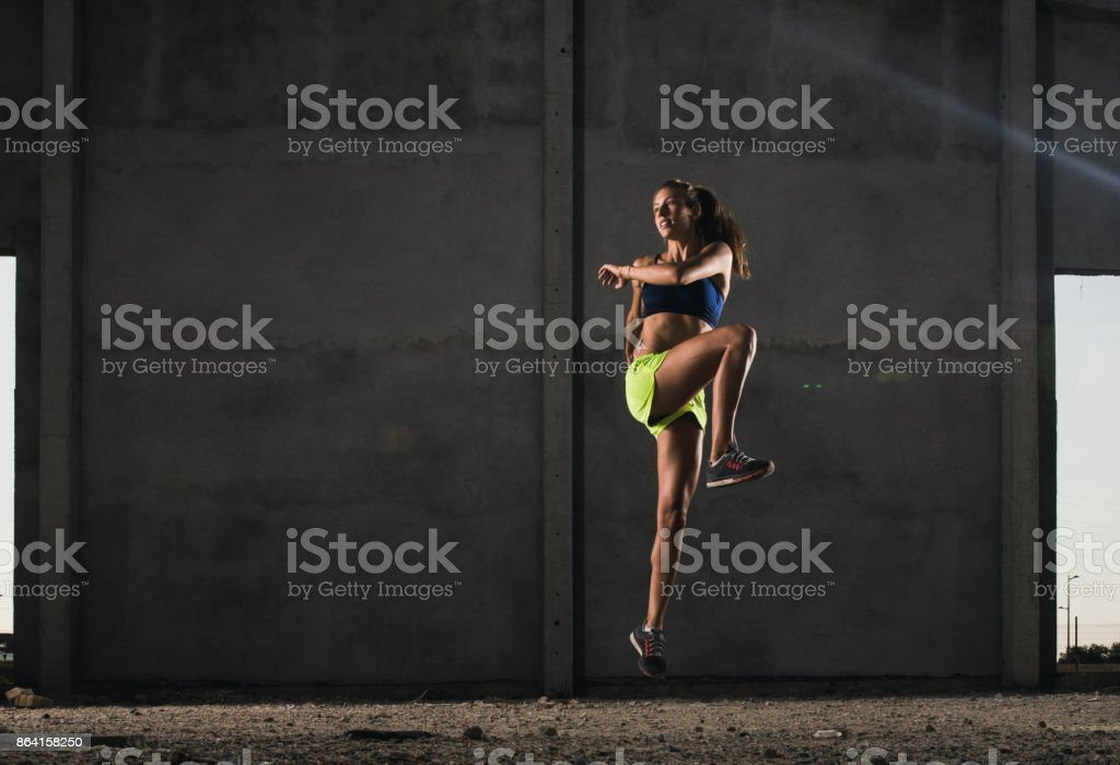 Female athlete jumping and warming up during cross training. royalty-free stock photo