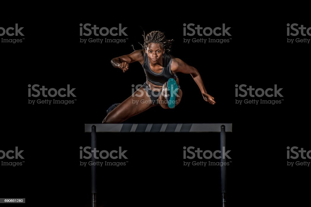 Female athlete jumping over a hurdle at night royalty-free stock photo