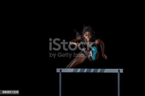 Front view of a female african-american athlete jumping over a hurdle. Black background.