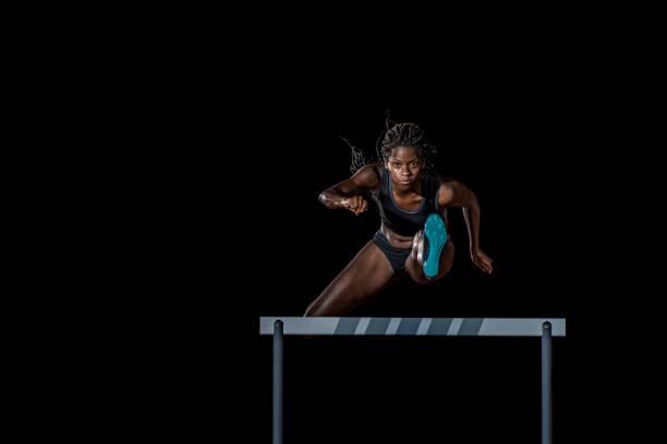 Atleta feminina, saltando sobre um obstáculo. - foto de acervo