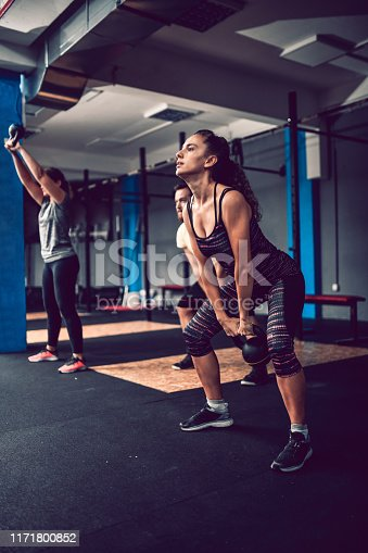 Female Athlete Lifting Kettlebell With Mighty Effort