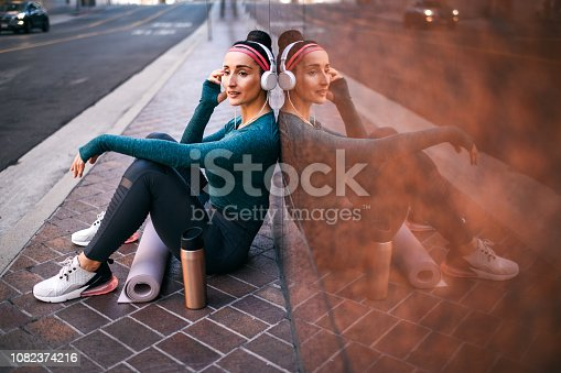 1091470492 istock photo Female athlete listening to music while sitting with her back against a marble building wall on a street sidewalk downtown 1082374216
