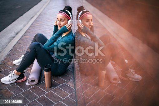 1091470492 istock photo Female athlete listening to music while sitting with her back against a marble building wall on a street sidewalk downtown 1091469858