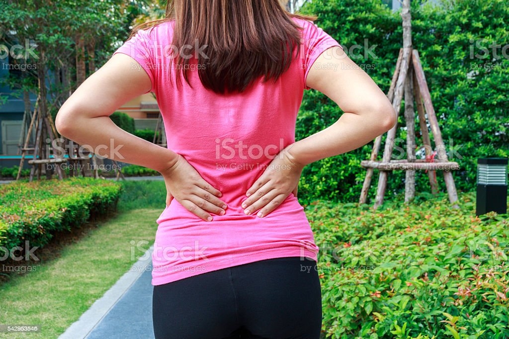 Female athlete lower back painful injury. Sporty woman backache stock photo