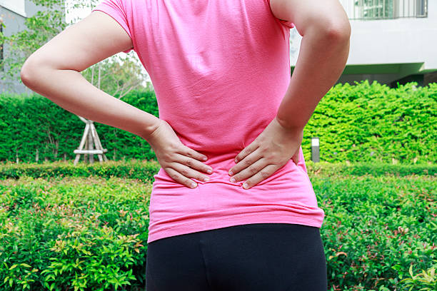 female athlete lower back painful injury. sporty woman backache - low section stock photos and pictures