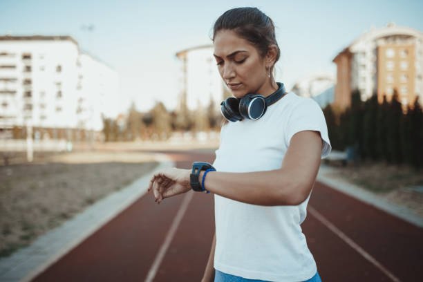 Female athlete measuring time while running stock photo