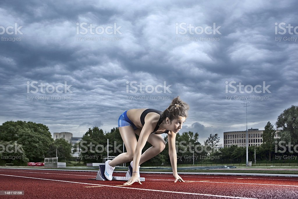 female athlete on a starting block royalty-free stock photo