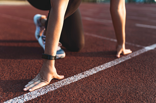 Woman athlete in starting position for running outdoors