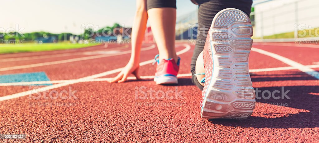 Female athlete on the starting line of a stadium track stock photo