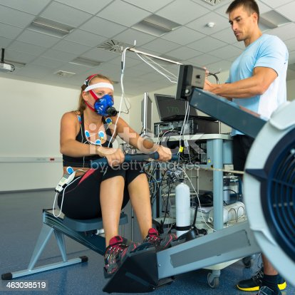 Female athlete having a VO2 test with a VO2 mask on her face, electrocardiogram pads attached, pulse rate 170 BPM, rowing machine