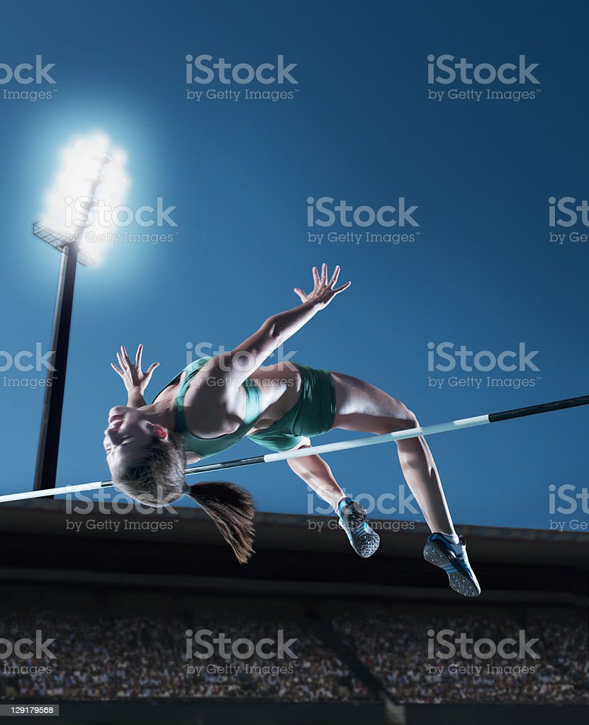 Female athlete performing high jump stock photo