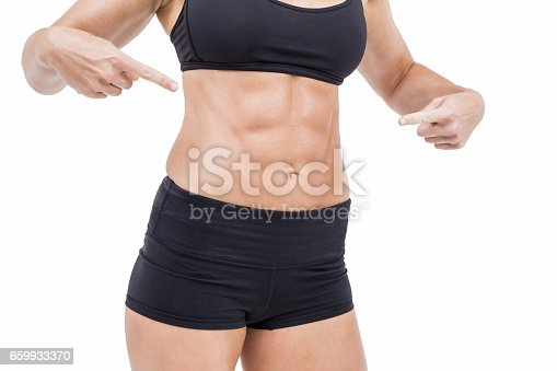Female athlete pointing her abs on white background