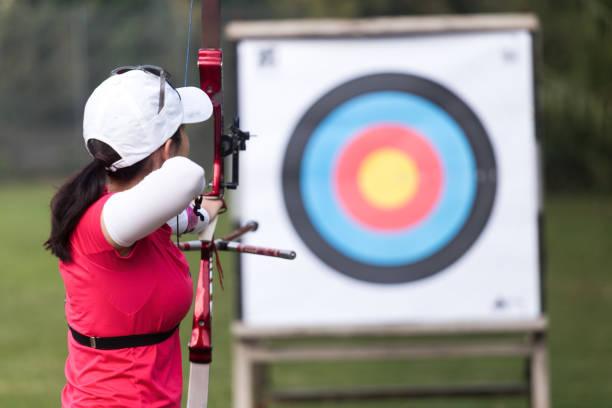 athlète féminin pratiquant le tir à l'arc dans le stade - tir à l'arc photos et images de collection