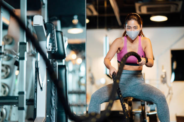 Female athlete practicing with battle rope while wearing protective face mask in gym stock photo