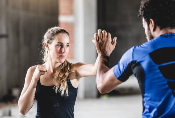 Female Athlete Practicing With Trainer Female Athlete Practicing With Trainer self defense stock pictures, royalty-free photos & images