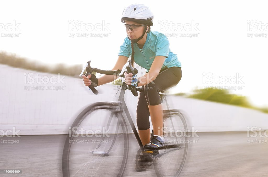 female athlete racing on a bike. motion blurred image royalty-free stock photo