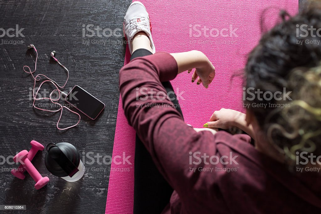 Female athlete resting on mat after achieved workout goals stock photo