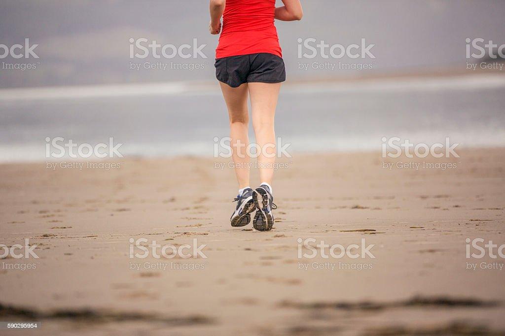 Female athlete running at the beach royaltyfri bildbanksbilder