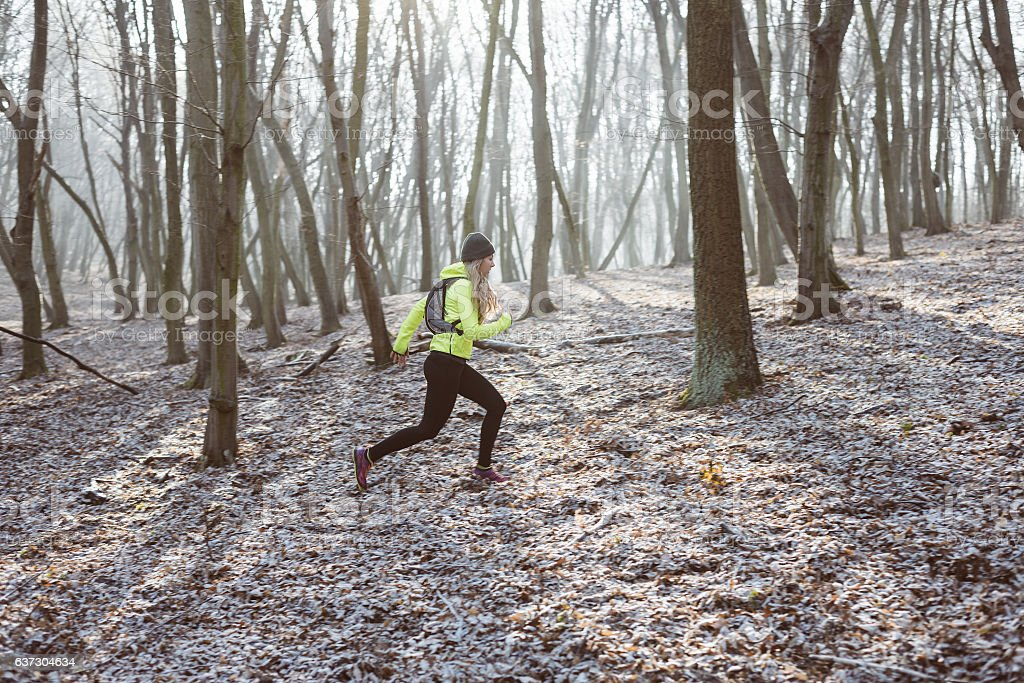 Female athlete running in the forest trail. stock photo