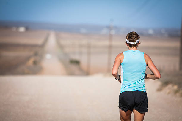 Female athlete running on a dirt road stock photo