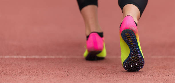 Female athlete running on stadium track Female athlete running on stadium track, dynamic run of sprinter in a stadium women's track stock pictures, royalty-free photos & images