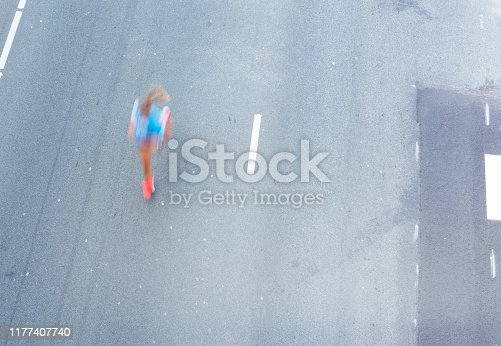 Blurred motion high angle image of an athlete woman running on the road.