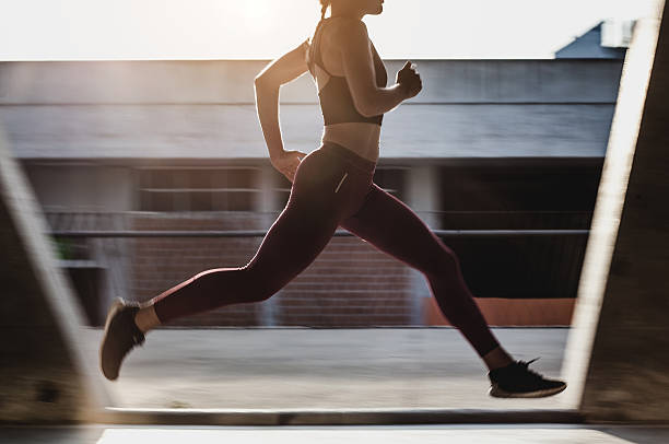 Female Athlete Running Outdoors Female Athlete Running Outdoors cardiovascular exercise stock pictures, royalty-free photos & images