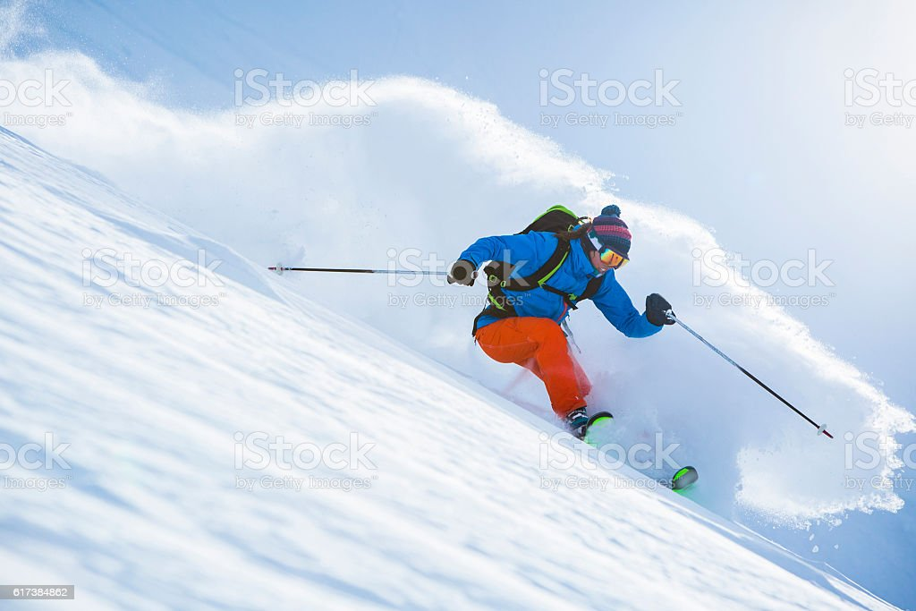 Female athlete skiing in deep powder. stock photo