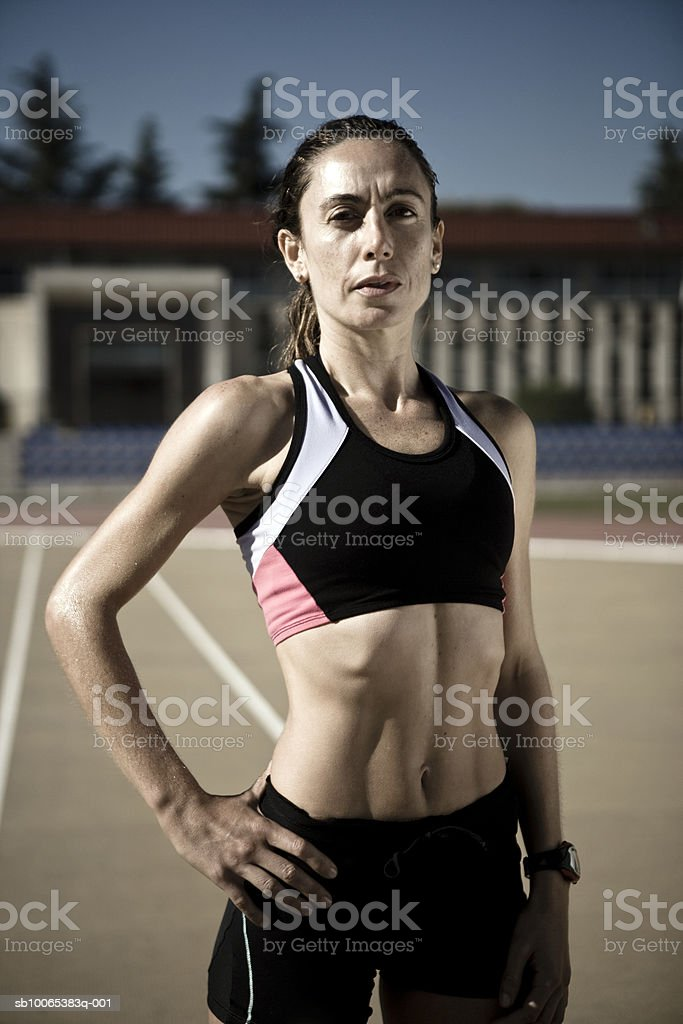 Female athlete standing with hand on hip in stadium, portrait, close-up royalty-free stock photo
