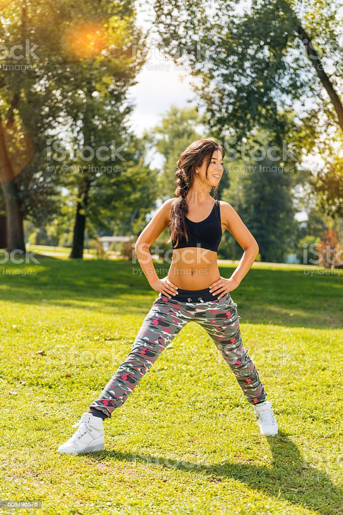 Female athlete stretches legs and body after outdoor training session royalty-free stock photo