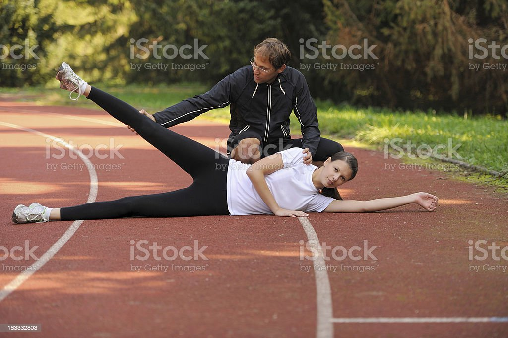 Female athlete stretching assisted by her coach royalty-free stock photo