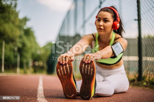 520047182istockphoto Female Athlete Stretching Outdoors and listening music 969624730