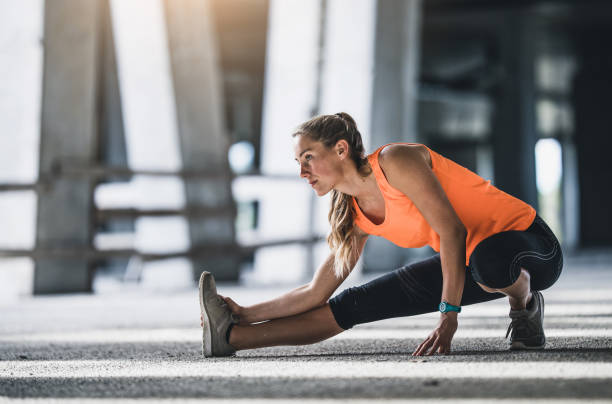 female athlete stretching outdoors - stretching stock photos and pictures