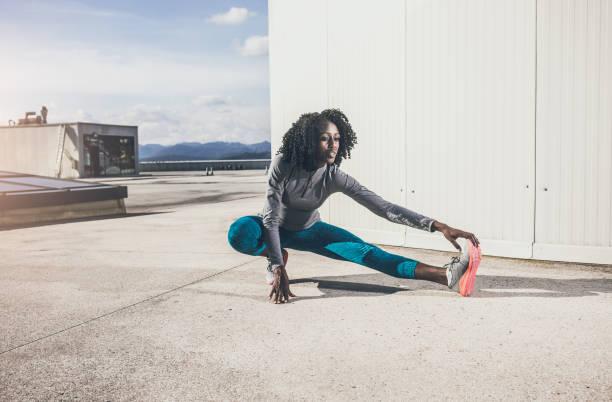 Atleta mujer estiramiento al aire libre - foto de stock