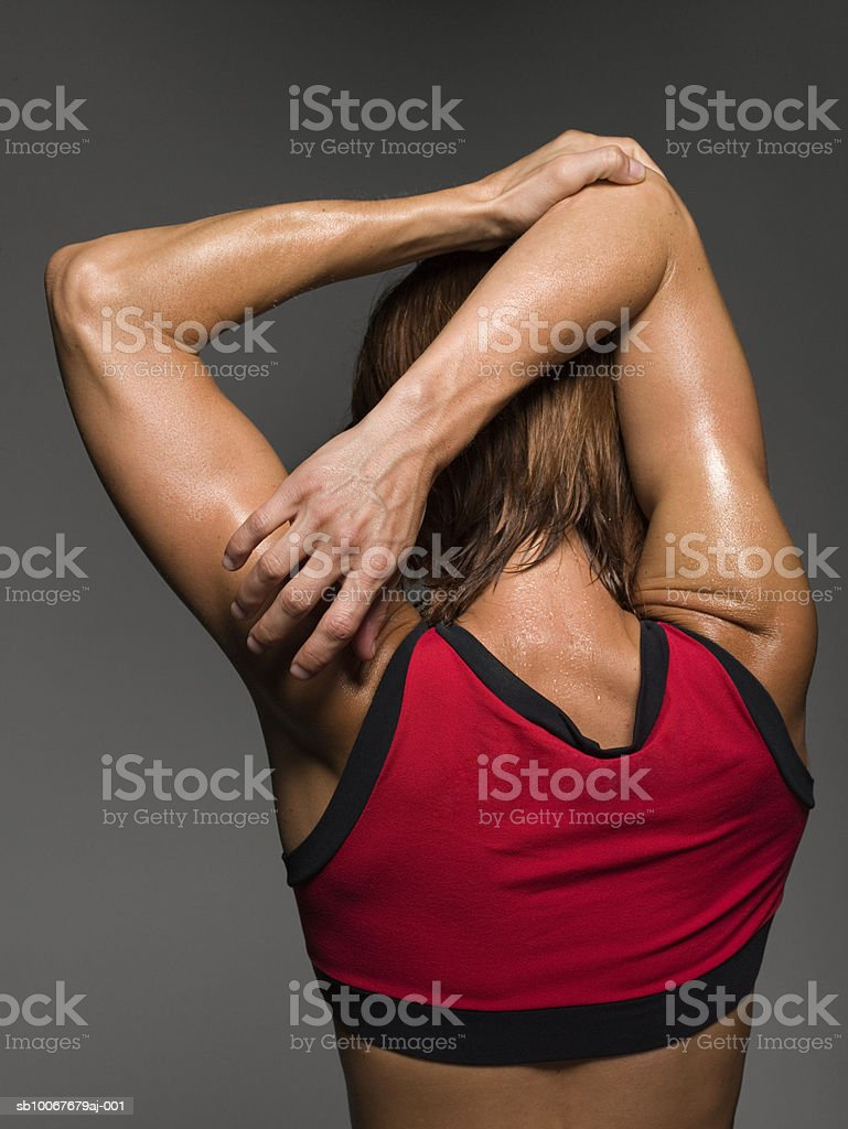 Female athlete stretching, rear view, studio shot royalty-free stock photo