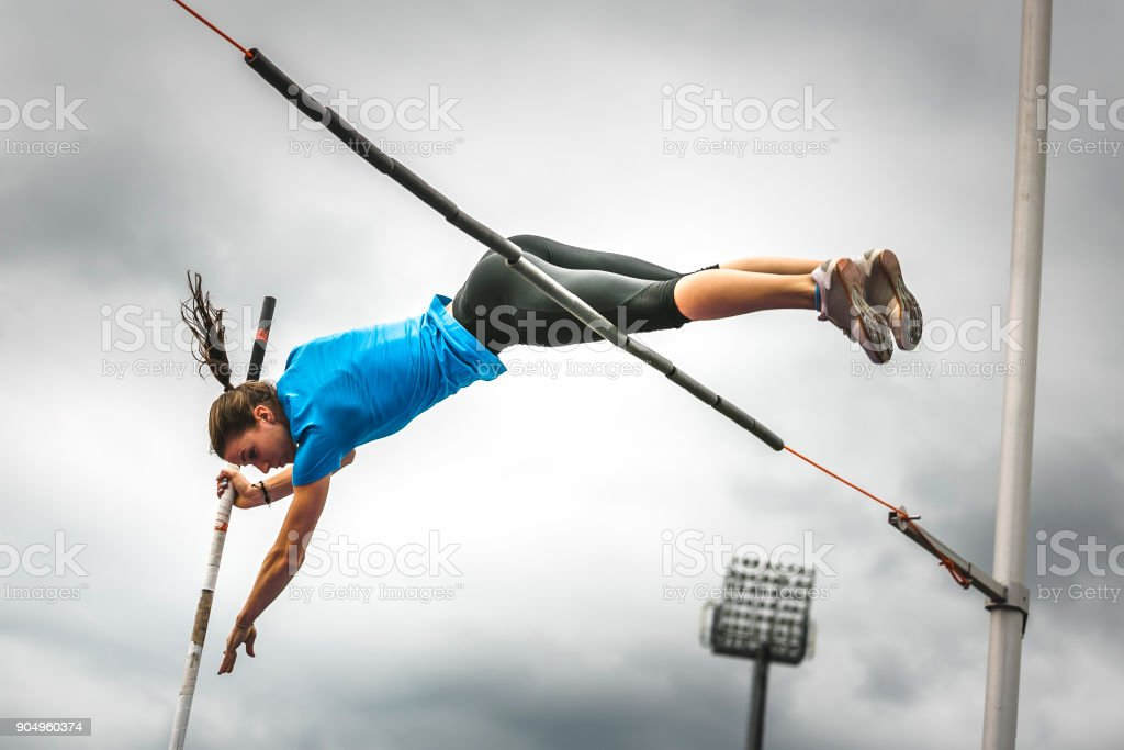 Female athlete successful attempt bar clearance stock photo