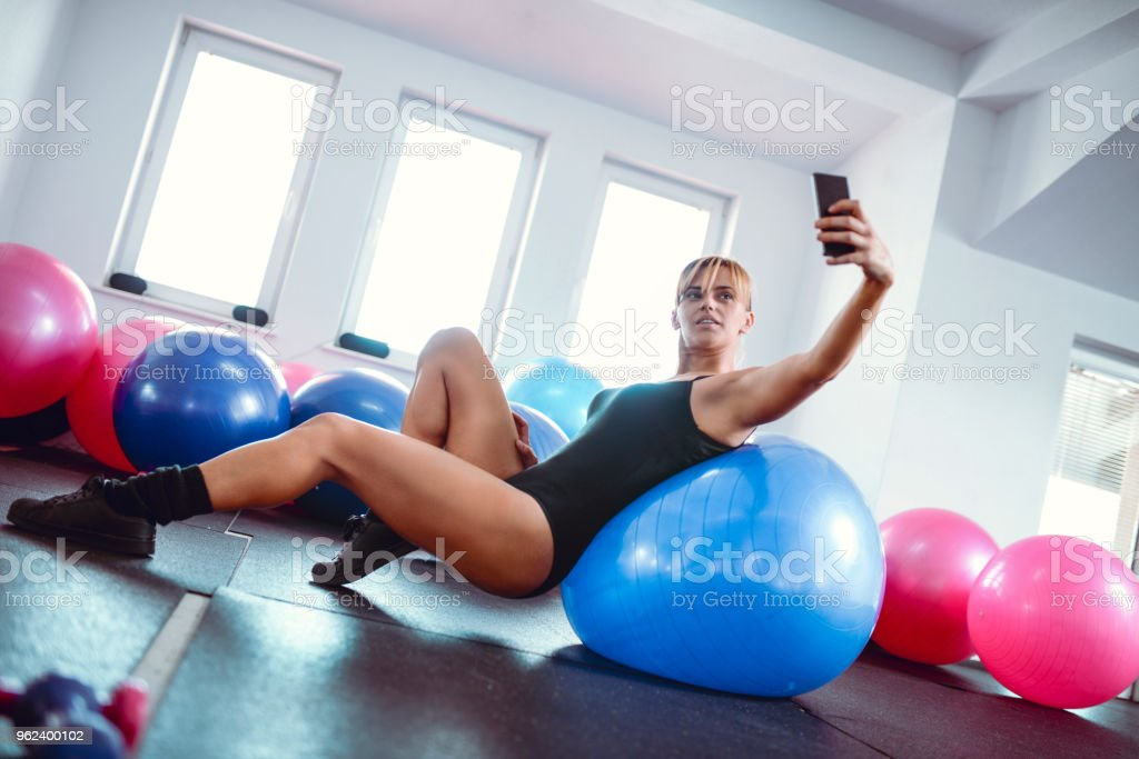 Female Athlete Taking Selfie While Resting After Workout In Gym stock photo