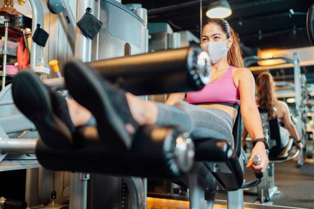 Female athlete training her legs in gym while wearing protective face mask stock photo