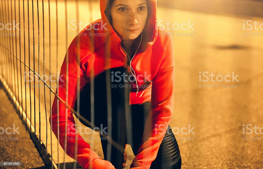 Female Athlete Tying her Shoes and Preparing Herself for Jogging photo libre de droits