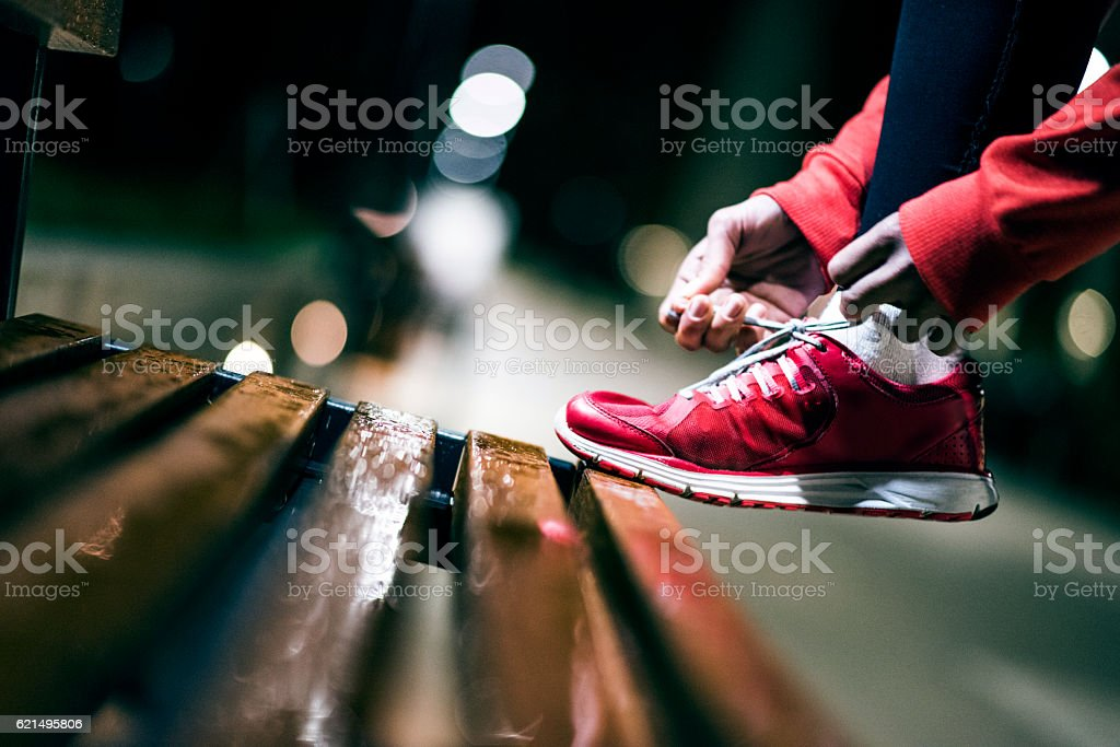 Female athlete tying her sneakers photo libre de droits