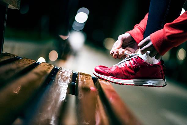 female athlete tying her sneakers - sitzbank schuhe stock-fotos und bilder