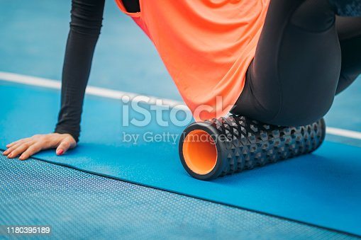Close up image of attractive female athlete, stretching with foam roller, outdoors