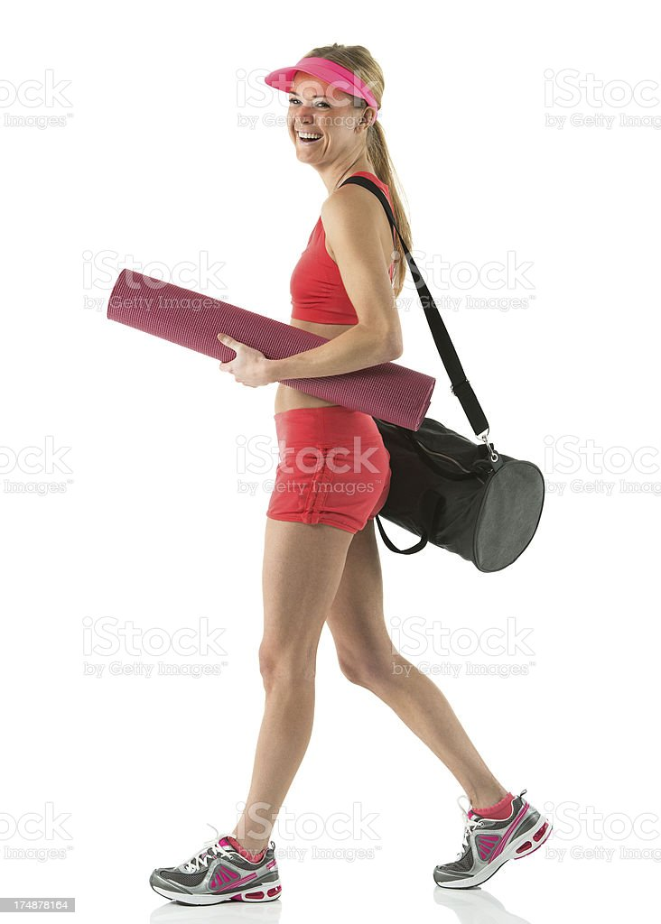 Female athlete walking with yoga mat and bag royalty-free stock photo