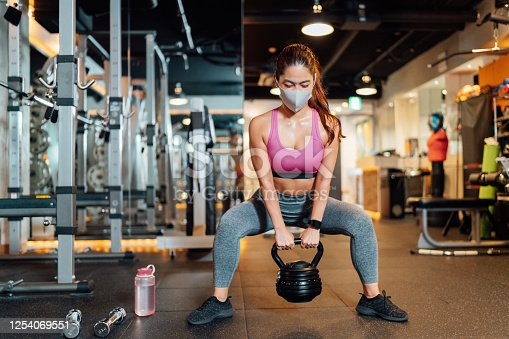 A female athlete is wearing a protective face mask and lifting a kettlebell in a gym.