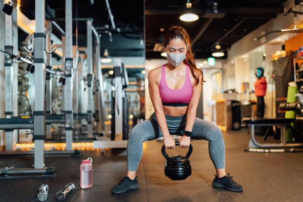 Female athlete wearing protective face mask and lifting kettlebell in gym stock photo