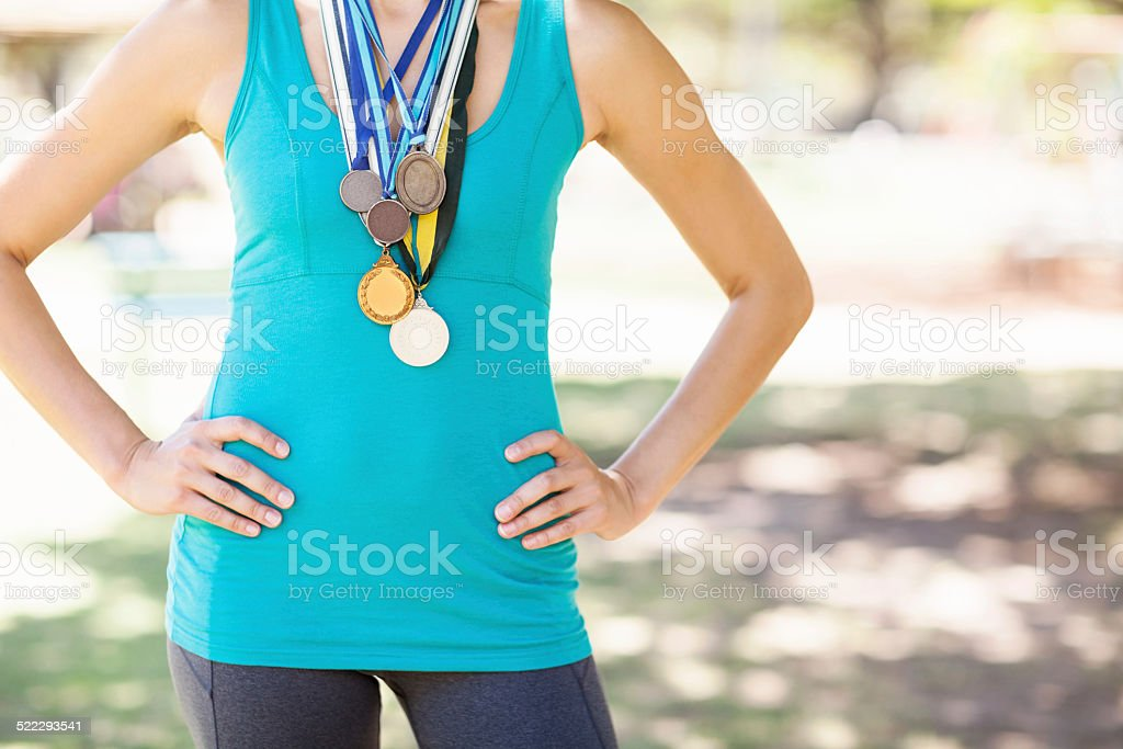 Female Athlete Wearing Various Medals At Park stock photo