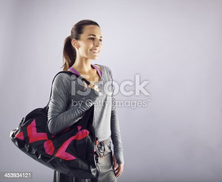istock Female athlete with gym bag looking away smiling 453934121
