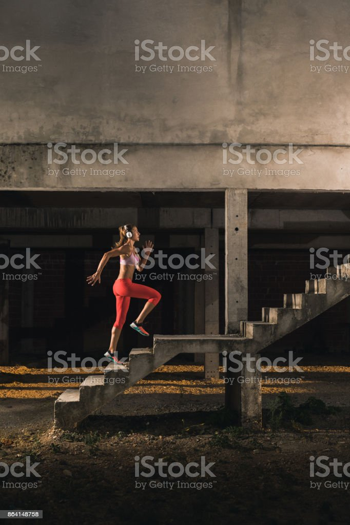Female athlete with headphones running up the stairs in old ruin. royalty-free stock photo